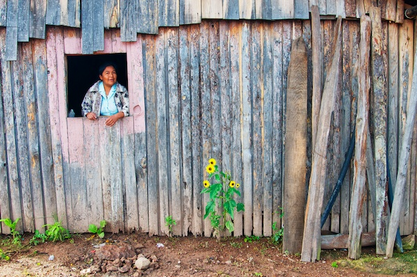 Old building with woman and flowers in Cerocahui, Mexico by Ralph Velasco.