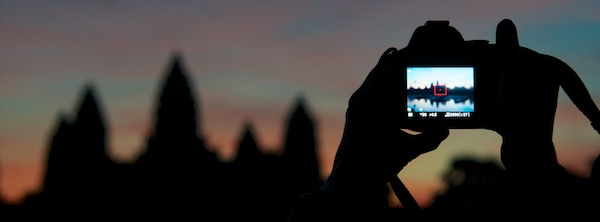 Angkor Wat at sunrise with person taking picture - Siem Reap, Cambodia by Ralph Velasco