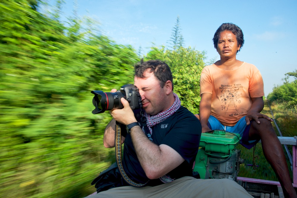 Brian Cruickshank shooting on the bamboo train near Battambang, Cambodia by Ralph Velasco.
