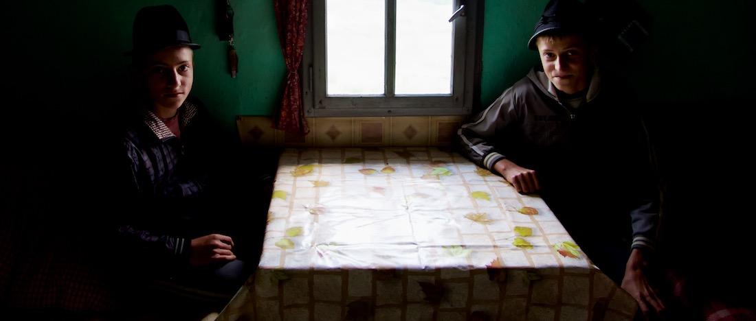 Gabi and Nicu at Kitchen Table of Sheepfold - Jina, Romania by Ralph Velasco