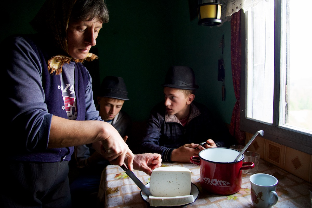 Ileana cutting sheep's cheese in home at sheep fold near Sibiu, in Transylvania, Romania - Copyright 2014 Ralph Velasco